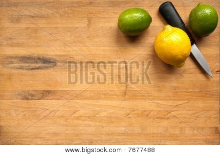 A Pair Of Limes And A Lemon With a knife On A Cutting Board