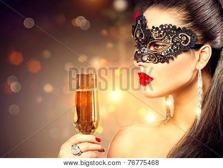 Sexy model woman with glass of champagne wearing venetian masquerade mask at party, drinking champagne over holiday glowing background. Christmas and New Year celebration