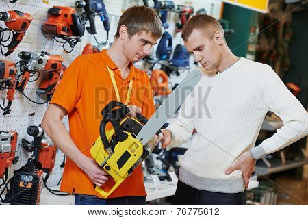 Sale assistant demonstrating electric chail saw to young man in electrical appliance shopping mall supermarket
