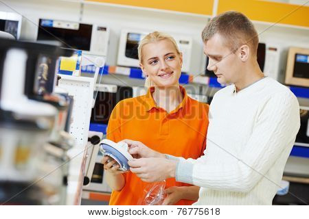 Young man choosing electric blender in home appliance shopping mall supermarket