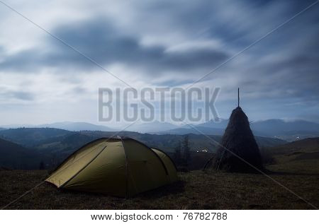Night landscape with tourist tent in the mountain village. Carpathian mountains, Ukraine, Europe