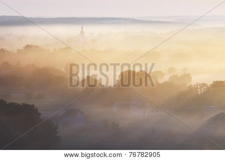 Morning landscape with mist over the river. Dome of the Church in the fog