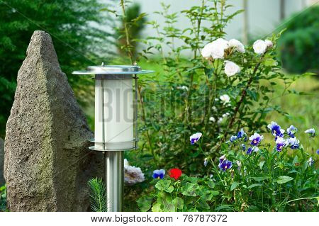 Solar Powered Lamp On Garden Background.