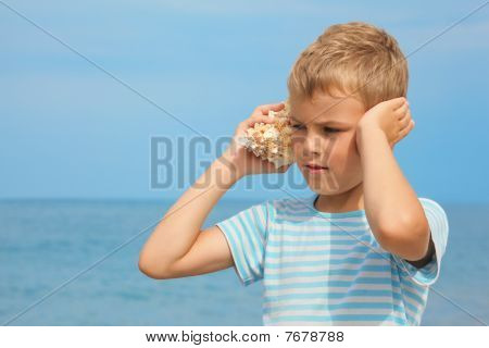 little boy with shell listening noise of sea.