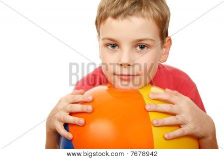 Portrait of boy with large inflatable ball on white
