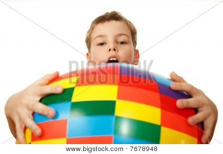 Boy holds before itself big inflatable multi-coloured ball