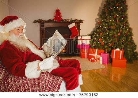 Santa claus reading newspaper on the couch at home in the living room