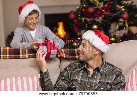 Father giving his son a christmas present at home in the living room