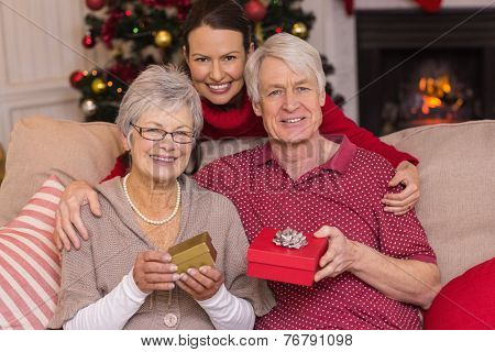 Mother posing with grandparents at christmas at home in the living room