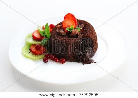 Hot chocolate pudding with fondant centre with fruits, isolated on white