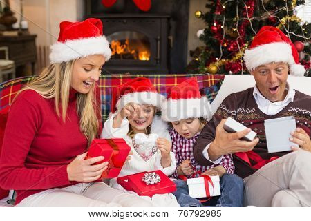 Festive shocked family exchanging gifts at home in the living room