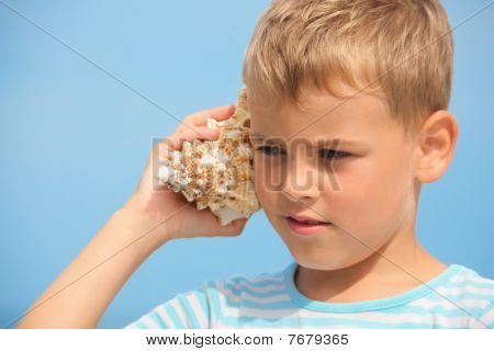 little boy with shell listening noise of sea