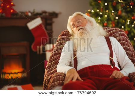 Santa claus napping on the armchair at home in the living room