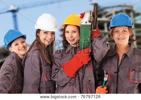 Four yung women wearing work clothes and helmets isolated with work path in front of a construction background.