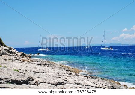 PAXOS, GREECE - JUNE 19, 2014: Sailing boats pass the rocky Arkoudaki beach at Lakka on the Greek island of Paxos. Lakka is the Northern port of the 13km long Ionian island.