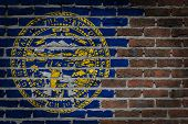 picture of nebraska  - Very old dark red brick wall texture with flag  - JPG