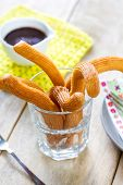 stock photo of churros  - Homemade Churros in a glass by chocolate sauce  - JPG