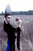 image of evil queen  - evil queen with an apple in the field - JPG