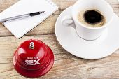 picture of prostitutes  - Ring for sex bell on wood table with coffee and notepad inthe background - JPG