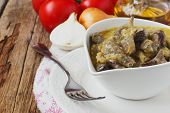 stock photo of stew  - stewed pork liver in a bowl and different vegetables on the dinner table  - JPG