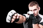 pic of kickboxing  - a young kickboxer or boxer isolated over a black background
