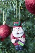 stock photo of adornment  - closeup of a Santa Claus handmade adornment decorating the Christmas tree hang from a golden ribbon - JPG