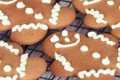 stock photo of gingerbread man  - Freshly baked gingerbread man cookies on cooling rack closeup - JPG