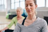 stock photo of yoga instructor  - Relaxed woman practicing yoga in gym with senior woman in background meditating - JPG