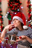 pic of finger-licking  - Woman tasting something licking her finger on Christmas - JPG