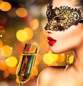 stock photo of masquerade mask  - Sexy model woman with glass of champagne wearing venetian masquerade mask at party - JPG