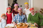 stock photo of extended family  - Happy extended family in party hat at dinner table at home in the living room - JPG