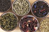 image of black tea  - Assortment of dry tea in ceramic bowls - JPG