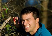 pic of dog-rose  - Attractive man picking up dog roses in forest - JPG