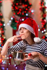 stock photo of finger-licking  - Woman tasting something licking her finger on Christmas - JPG