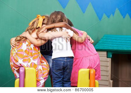Children in kindergarten going into huddle to hold a council of war