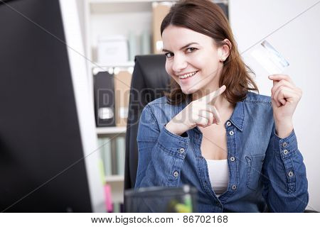 Smiling Office Woman At Her Table Showing A Card