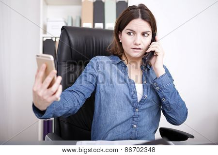 Woman Talking On The Phone And Checking Her Mobile