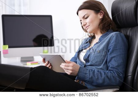 Puzzled Businesswoman Studying Her Tablet