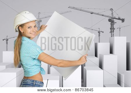 Girl in helmet showing empty paper sheet. White cubes with tower cranes