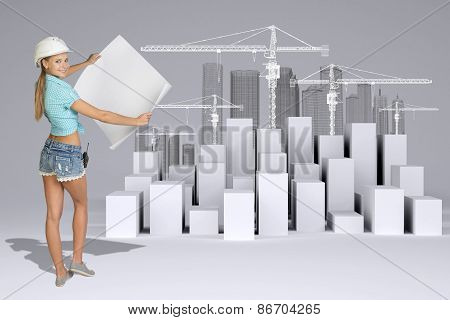 Girl in helmet showing empty paper sheet. Full lenght. White cubes with tower cranes