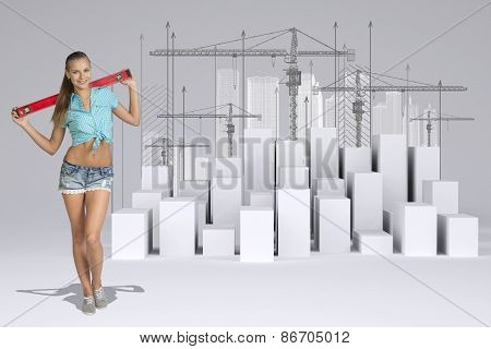 Worker holding builders level on shoulders. White cubes with tower cranes