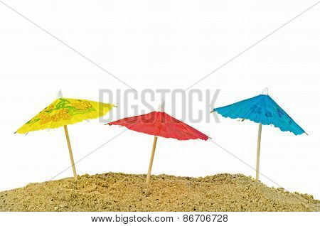 Miniature paper sun umbrellas in sand
