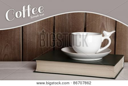 Old book and cup of coffee on table