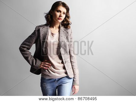 Portrait of beautiful model in jeans and jacket on gray background
