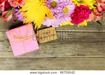 Mother's Day gift with tag and flowers on wood
