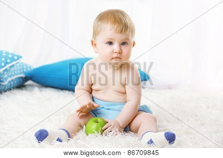 Cute baby boy  with green apple on carpet, on light background