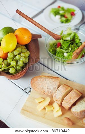 Fresh fruits, vegetable salad, cut bread and cheese on table