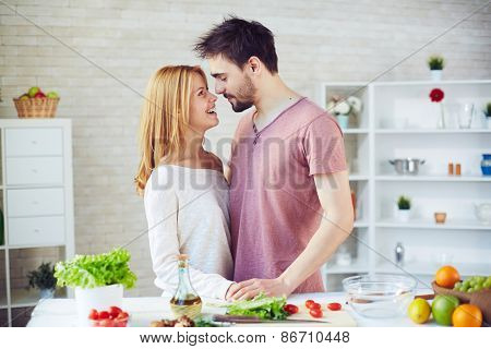 Happy young couple of vegetarians flirting in the kitchen