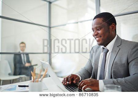 African businessman in formalwear typing on laptop