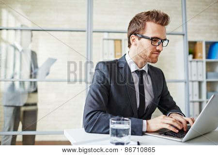 Young businessman in formalwear typing on laptop